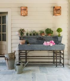 A large oversize soapstone sink designed by Rosney Co. provides a great place to arrange flowers or to wash up before going inside of the 2015 Southern Living Charlottesville Idea House.