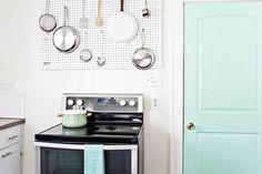 Kitchen - pegboard and mint door Kitchen Utensil Organization, Kitchen Pegboard, Kitchen Utensils, Mint Door, Pan Storage, White Subway Tile Backsplash, Dark Wood Cabinets, Linoleum Flooring, Wood Countertops
