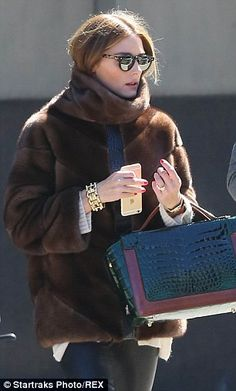 Accessories queen: The 29-year-old finished off her look with chunky gold jewellery, a chic bag and some retro shades
