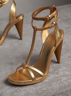 A pair of smooth metallic leather sandals punctuated with polished rivets. The style is kept feminine with slender T-bar straps and a high cone heel.