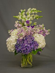 An abundant garden arrangement of white and purple hydrangea, lavender stock, purple lisianthus, and white snapdragons in a tall cylinder vase. Purple Wedding Arrangements, Table Arrangements, Tall Cylinder Vases, Hydrangea, Glass Vase, Home Decor, Desk Arrangements, Decoration Home, Room Decor