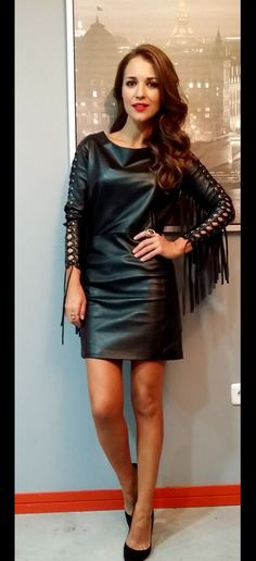 Amateur in black leather minidress with fringed sleeves