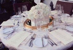 An early summer wedding reception. Round table, oval mirror, rectangular ceramic container - and a lucious arrangement of ivory roses and hydrangea.  WWW.DavidRohrStudio.com