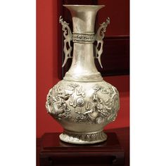 Silver Decorative Dragon Vase.  This silver casted vase features rich details in the handles, ornamental bands, and relief scene with dragons that spreads across the vase body. Chinese style decor.