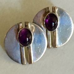 Beautiful, mirror finish silver disks with brass highlight and amethyst stone.  Very modern, clean  look