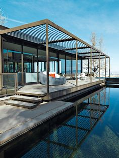 The house's slatted, anodized aluminum canopies and indoor-outdoor spaces flow into one another. The resin Opal lounge and Square Cube table, with pillows and cushions covered in Sunbrella fabrics, and the teak and powder-coated cast aluminum Silver Dining swivel rocker, are all from the Veneman Collections.  Photo by: Jill PaiderCourtesy of: Jill Paider