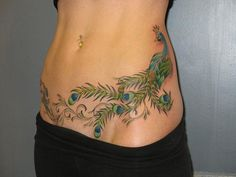 A blue and green peacock bird tattoo stretched across the hips and abdomen.
