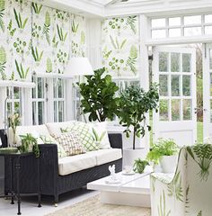white and green conservatory with seating area and green leaf fabrics and blinds