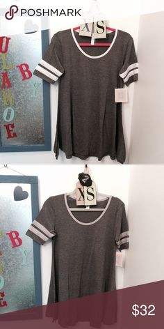 Perfect T Tee Shirt by Lularoe Cute stripe detail in this Perfect T made from comfortable spun polyester jersey. The Perfect T has a swing shape and side slits to compliment any figure! The flattering half sleeve is a favorite of many LLR fans! This top is a charcoal gray with accenting racing stripes. Runs 1-2 sizes large. LuLaRoe Tops Tees - Short Sleeve