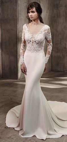 Featuring a soft, unlined tulle and lace illusion bodice and illusion scoop over plunging V-neckline, this full-length mermaid gown is completely modern and sexy with a timeless feel. The long, delicate sleeves embellished with the most stunning lace designs are entirely contemporary yet classic along with the sleek stretch crepe skirt. A gorgeously ornate illusion, low V-back with crystal buttons trailing down the center is a symmetrical work of art. Finished with an invisible zipper…