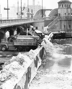 2 days after the historic 1967 storm, trucks operated by city crews dump loads of snow into the Chicago River near Wells Street and Wacker Drive.