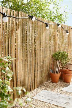 Le compromis entre le côté déco et l'intimité dans un jardin : le bambou. Aussi esthétique que pratique, il est peu cher et apportera un aspect naturel à votre espace extérieur. #bambou #brisevue #cours #guirlande #lumineuse #pots #plantes #castorama #inspiration #decoration #ideedeco #tendancedeco #jardin #exterieur #amenagement #vegetal #cloture