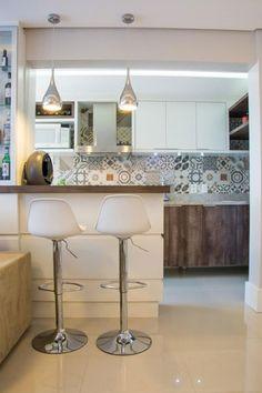 A cozinha com armários brancos e madeira ficou completa com a aplicação de revestimento hidráulico para destacar o espaço. Projeto de Camila Chalon.