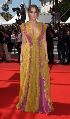 "To the ""American Honey"" premiere at the Cannes Film Festival, Riley Keough wore a Gucci Cruise 2016 silk georgette and chantilly lace ruffled gown with gold sandals by Alessandro Michele."