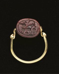 A WESTERN ASIATIC RED STONE SCARABOID FROM THE LYRE-PLAYER GROUP   LATE 8TH CENTURY B.C.   Engraved with a standing ibex, with curved horns, a bird perched on his rump, circle and stylized plant in the field, in later swivel ring setting, 1.6 cm. long, 2.1 cm. across inner hoop