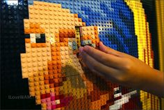 """The last pieces of about 5,000 Lego blocks are added by elementary school girl to complete a reproduction of Jonannes Vermeer's masterpiece """"Girl with a Pearl Earring"""" in Tokyo Thursday, Aug. 9, 2012. A total of 380 children participated in a nine-day workshop to create the Lego art at the newly opened Legoland Discovery Center to mark the 380th anniversary of the Dutch painter's birth and the exhibition of the original painting from the Royal Picture Gallery Mauritshuis at Tokyo Art Museum"""