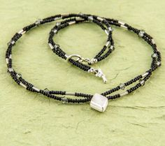 Short, dainty and elegant necklace made with black seed beads, sterling silver drop focal, sterling silver tube beads and Swarovski crystals. By Artigiana Designs - handmade artisan jewelry. $36.00, via Etsy.