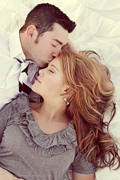 laying down, his head propped up on his hand, kissing her head