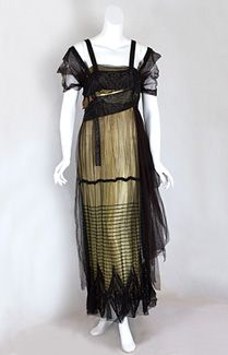 B. Altman beaded gold lamé evening dress, c.1915. With its luxe textiles and graphic, asymmetrical design, the brilliant dress has a powerful presence. The outer layer of black silk tulle is sculpted with asymmetrical draping and floats over a straight gold lamé under dress. The bodice is decorated with wide panels of black glass beads, beaded shoulder straps, and beaded hanging tassels. The skirt has horizontal rows of black beads as well as a spectacular beaded hem border of large…