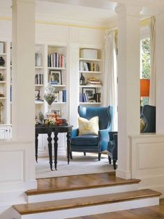 ahhhh. that blue leather chair, the white columns, white bookshelves, light streaming in. perfect.