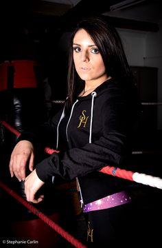 Model wears S.H crop zip up hoodie in black with purple waist embroidered exercise leggings.