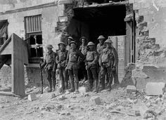 A group portrait of New Zealand Riflemen standing in the doorway of a ruined house on the outskirts of Bapaume just after its capture, August 1918.