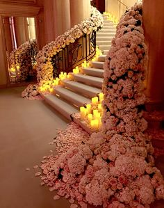 Amazing floral covered staircase with candles lighting the way