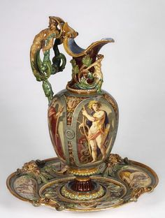 MINTON historicism ewer and under plate manufactured for the 1862 International Exhibition in London, majolica glazed, featuring Neoclassical panels depicting the labors of Hercules, figural merman handle, masks and mermaid