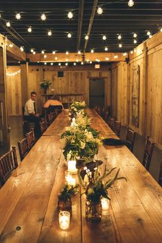 Such a lovely and chic wooden table setting with lush greenery at the center