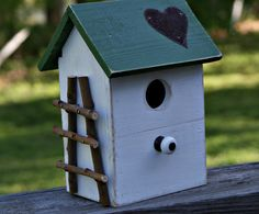 white birdhouse with green heart roo