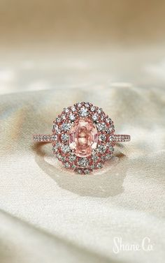 This halo setting is highlighted by 56 round diamonds, at approximately carat total weight, hand-selected for superior brilliance and pave-set in quality 14 Platinum Jewelry, Sapphire Jewelry, Diamond Jewelry, Oval Diamond, Round Diamonds, Peach Sapphire, Halo Setting, Halo Diamond Engagement Ring, Halo Rings