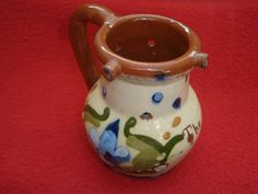 """Torquay Motto Ware Tormohun Longpark Scandy Puzzle Jug:   Produced by the Longpark Pottery in the early part of the 29th century , the Tormohun jug is of baluster form with applied handle , multiple holes to the body and three spouts. The body features Scandy decoration and the words """"The weakest goes to the wall"""".   Dimensions: 10.5 cm high - Condition: One spout missing and some glaze loss to the body - Stock Number: B017 - Price: £15.00"""