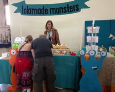 Lolamade Monsters uses vertical scale to draw attention to her booth. See more examples of attention-getting booths at Hip Hip Handmade Shows.