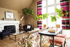 """Demonstrating her penchant for a patternful mix, a sofa upholstered in Lee Jofa fabric (""""big, old-lady florals are kind of my thing,"""" says Chloe) riffs off curtains made from Élitis's India fabric."""