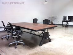 Hure work table with a walnut top by Vintage Industrial Furniture. Chairs are Aeron by Herman Miller.
