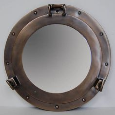 "The perfect nautical accent to any room in your exceptional coastal home. The Bronze Finish Cabin Porthole Mirror is a replica of a the porthole from which one views the world below deck. Made by gifted craftsmen, the mirror is crafted from aluminum with a bronzed finish and measures 15 inches in diameter and 2.75"" in depth."