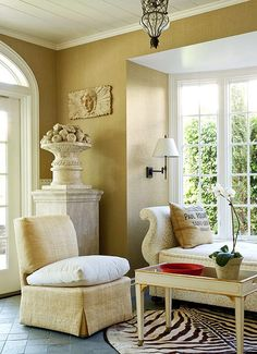 Sunshine filters in to this neutral sitting room making it a perfect spot to sit and relax. Love the wall color.