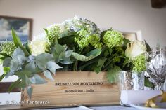Beautiful flowers placed in the Brunello di Montalcino's original wooden box, decorating the dinning table of a countryside wedding