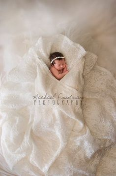 Newborn baby in Mom's wedding dress