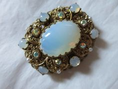 $11.30 2016 Ornate lacy, layered gold tone repousse frame with bluish moonglow glass cabochons, aurora borealis rhinestones and faux pearls. In very good vintage condition. Marked W. Germany. Please view pictures