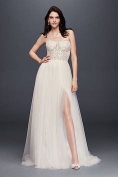 This gown is perfect for the bride who doesn't want to choose between traditional romance and alluring details. Its bustier-style illusion bodice is crafted of beaded sequined lace, while the side-slit, A-line tulle skirt reveals a bit of leg.   Galina Signature, exclusively at David's Bridal  Polyester  Sweep train  Back zip; fully lined  Dry clean  Imported  Also available in extra length