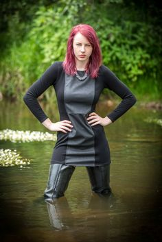 Redhead in multimedia black leather minidress and Acquo style rubber thigh boots waders in the water