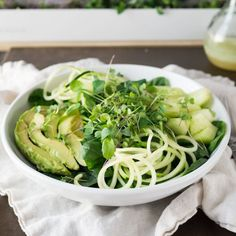 A crisp, refreshing spinach salad with spiralized cucumber, avocado and honeydew melon crowned with homegrown microgreens.