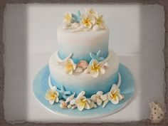 Ombre' Blue beach themed wedding cake........... 2 Tier Round (6 & 9 Inch) Wedding cake, Covered in White fondant and decorated with ombre' blue dusting, with white fondant rolls around the base of each tier, and Fondant shells with sugar frangipanis decorating each tier.