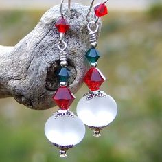 The Frosted Christmas handmade earrings were created with artisan frosted white lampwork glass beads, Siam red Swarovski crystals, emerald green Swarovski crystals, pewter bead caps and sterling silver
