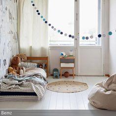 Dieses minimalistische Kinderzimmer ist nur mit dem Wichtigsten eingerichtet und doch hat es eine angenehme Ausstrahlung und wirkt behaglich. Die Mustertapete  …