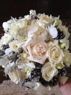 Rustic winter wedding flowers including roses, ranunculas, cosmos, berries, pine cones and dusty miller.