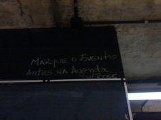 Indicação escrita em giz branco para a agenda fixada na parede atrás da papelaria da FAU, indicando a possibilidade de se marcar eventos em um calendário que todos podem usufruir. Destina-se, portanto, a todos os participantes dos eventos da faculdade.