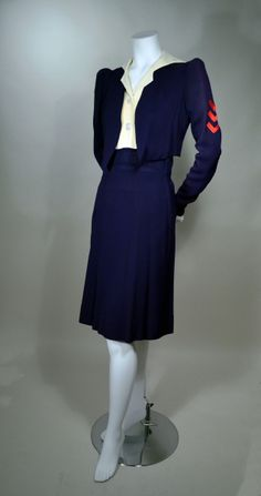 Early 1940s two-piece dress: Navy blue and cream drapey rayon crepe with red embroidered trim. Two-tone dress: cream shirt style bodice with notched V-neck middy collar and faux button front (2-mother-of-pearl). Short puff sleeves with pleated cap and self shoulder pad in cap. Wide waist inset. Six gore A-line skirt. Navy cut-away bolero jacket. Three applied red embroidered rank chevrons. Via RP Vintage.