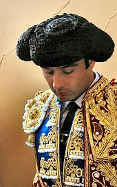 """A montera is the hat traditionally worn by many males and females in the folk costumes of the Iberian peninsula. It has come to name also but not exclusively the ones used by bullfighters, introduced to the ritual event in 1835 by Francisco """"Paquiro"""" Montes"""